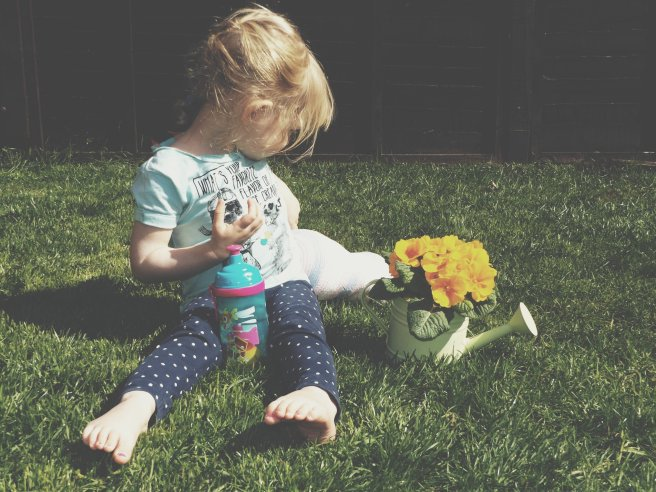 Little girl in the grass with a watering can plant pot
